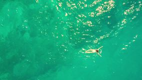 El top de la antena abajo tiró de una natación de la mujer joven en el mar Fotografía de archivo libre de regalías