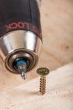 El tornillo de metal atornilló en un tablero de madera Imagen de archivo