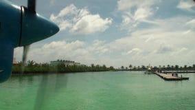 El tornillo del avión amarillo-azul hace girar en el fondo del embarcadero en el Océano Índico almacen de metraje de vídeo