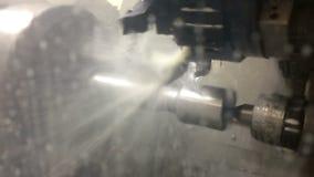 El torno con los procesos del CNC un cortador un detalle de acero En el proceso del detalle se utiliza un líquido de enfriamiento almacen de metraje de vídeo