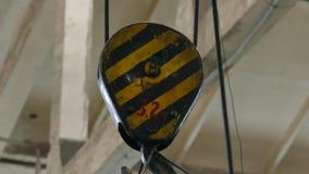 El torno de la grúa levanta la carga en la fábrica Los ganchos de acero sostienen una placa de acero pesada metrajes