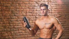 El torso desnudo de With del atleta bebe el agua de la botella de los deportes almacen de video