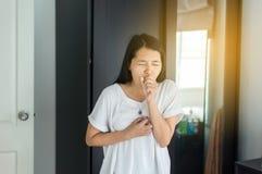 El toser de la mujer y dolor de pecho asiáticos jovenes, concepto de salud imagenes de archivo