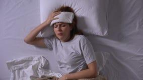 El toser enfermo de la muchacha, mintiendo en cama con la compresa mojada en la frente, gripe estacional almacen de video