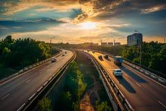 El tráfico de ciudad en la carretera de asfalto o la ruta de la carretera en el tiempo de la puesta del sol, porción de coches co foto de archivo