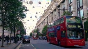 El tráfico, los taxis y el autobús de dos pisos rojo Londres transporta la conducción de último Selfridges, calle de Oxford, Lond almacen de metraje de vídeo