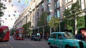 El tráfico, los taxis y el autobús de dos pisos rojo Londres transporta la conducción de último Selfridges, calle de Oxford, Lond almacen de video