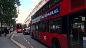 El tráfico, los taxis y el autobús de dos pisos rojo Londres transporta la conducción de último Selfridges, calle de Oxford, Lond metrajes