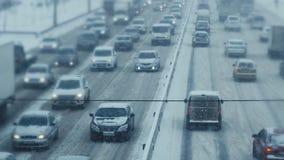 El tráfico por carretera con los coches va en un camino nevoso almacen de video