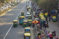 El tráfico urbano indio y los carritos amarillos verdes llevan en taxi el aparcamiento cerca de peatones y del comercio de calle, imagen de archivo