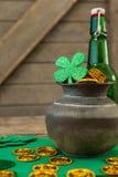 El trébol del día del St Patricks, la botella de cerveza y el pote llenaron de las monedas de oro del chocolate Fotos de archivo libres de regalías