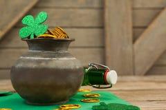 El trébol del día del St Patricks, la botella de cerveza y el pote llenaron de las monedas de oro del chocolate Fotografía de archivo