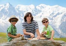 El trío (padre y dos hijos) tiene comida campestre Fotografía de archivo