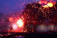 El tr?fico se ve a trav?s del parabrisas del coche cubierto en lluvia, fondo hermoso de la lluvia y de las luces imagen de archivo
