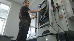 El trabajado cualificado de la visión inferior cierra la puerta de la máquina-herramienta almacen de metraje de vídeo