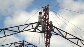El trabajador actúa el bloque de cadena para levantar para arriba los pedazos de acero Lapso de tiempo almacen de video