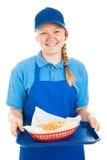 El trabajador adolescente sirve la hamburguesa y fríe Imagenes de archivo