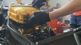 El trabajador ajusta el filtro de aire dentro de la moto almacen de video