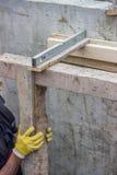 El trabajador ajusta llano de la instalación de madera del marco Foto de archivo libre de regalías