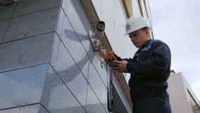 El trabajador ajusta el videcam montado en la pared del edificio con el instrumento almacen de video