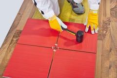 El trabajador aplica el azulejo en suelo Fotos de archivo libres de regalías