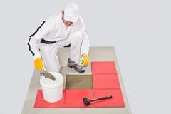 El trabajador aplica el pegamento del azulejo con la paleta hecha muescas en Imagenes de archivo