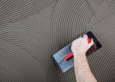 El trabajador aplica el pegamento para una teja en una pared Fotografía de archivo libre de regalías