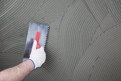 El trabajador aplica el pegamento para una teja en una pared Foto de archivo libre de regalías