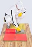 El trabajador aplica las baldosas cerámicas Foto de archivo libre de regalías