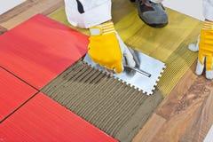 El trabajador aplica las baldosas cerámicas Imagen de archivo libre de regalías