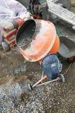 el trabajador auxiliar desarrolla un mortero del cemento en un mezclador concreto en la construcción de una casa de campo fotos de archivo libres de regalías