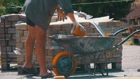 El trabajador carga una piedra de pavimentación coloreada en la carretilla metrajes