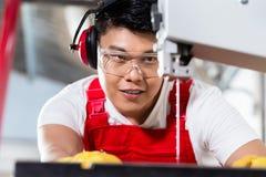 El trabajador chino encendido vio en fábrica industrial fotografía de archivo