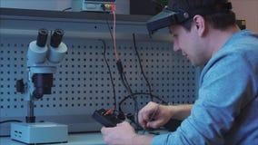El trabajador comprueba el funcionamiento del dispositivo Conecta los alambres almacen de metraje de vídeo