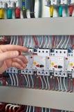 El trabajador comprueba la operación del gabinete eléctrico después de su producción imágenes de archivo libres de regalías