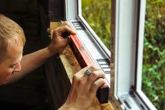 El trabajador comprueba el nivel de una ventana foto de archivo libre de regalías