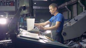 El trabajador comprueba el periódico impreso fresco en el equipo de la tipografía