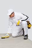 El trabajador con el cepillo de alambre limpia el substrato del cemento Imágenes de archivo libres de regalías