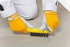 El trabajador con el cepillo de alambre limpia la base del cemento Foto de archivo