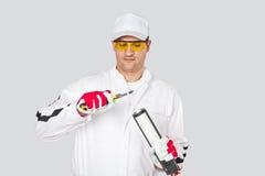 El trabajador con el cuchillo quita el silicio del sellante del casquillo del corte Foto de archivo