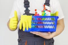 El trabajador con el equipo de la limpieza de la casa y los accesorios muestran el pulgar para arriba Imagen de archivo libre de regalías