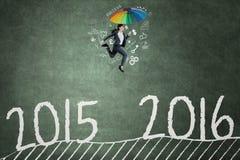 El trabajador con el paraguas salta sobre los números 2015 a 2016 Foto de archivo libre de regalías