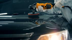 El trabajador con un buffwheel está esmaltando un coche negro metrajes