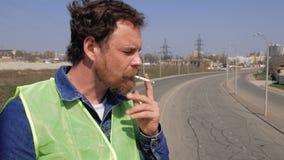 El trabajador con una barba y un bigote fuma en un puente en el fondo del autobahn v?deo 4K almacen de video