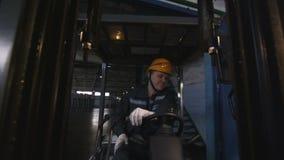 El trabajador conduce la carretilla elevadora más allá de mercancías a lo largo del primer del almacenamiento almacen de metraje de vídeo