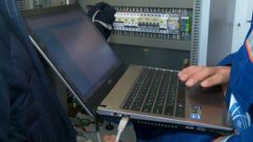El trabajador conecta el cuaderno con el equipo eléctrico del control en gabinete almacen de metraje de vídeo