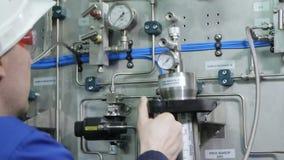 El trabajador conecta el dispositivo del manómetro con el panel de control  almacen de video