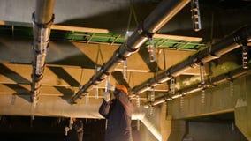 El trabajador conecta los detalles del metal con la tubería en la planta almacen de metraje de vídeo