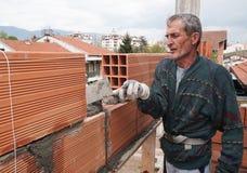 el trabajador construye una pared de ladrillo Imagen de archivo