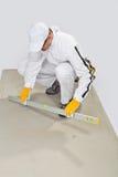 El trabajador controla la base del cemento Foto de archivo